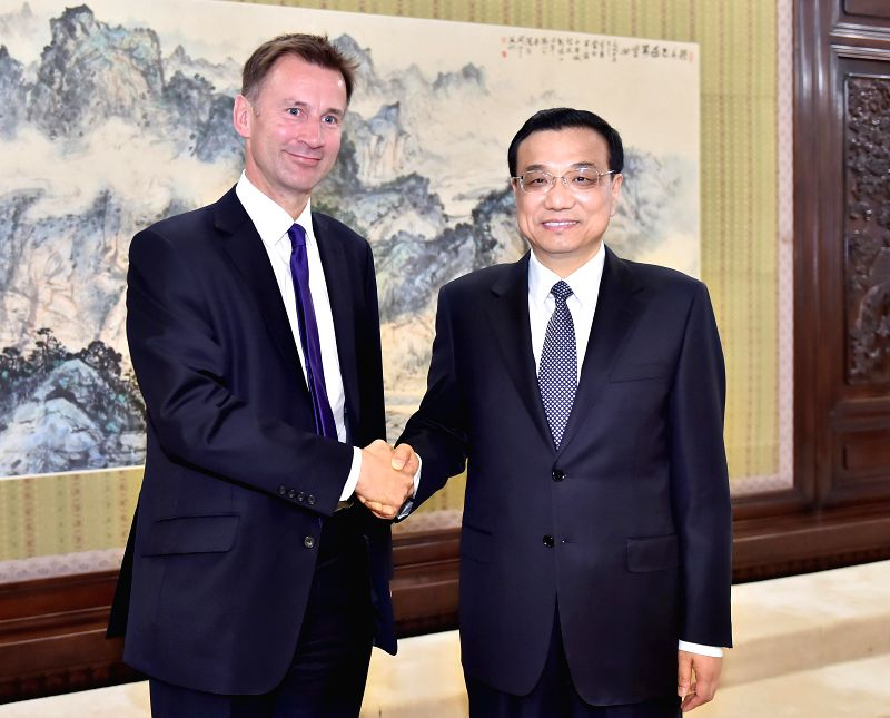 Chinese Premier Li Keqiang (R) shakes hands with British Health Secretary Jeremy Hunt in Beijing, capital of China, April 23, 2014. Jeremy is here to co-chair the .