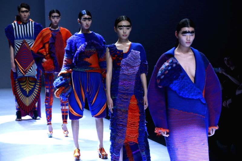 Models present creations designed by students from China Academy of Arts during the opening ceremony of the 2014 China Graduate Fashion Week in Beijing, capital of