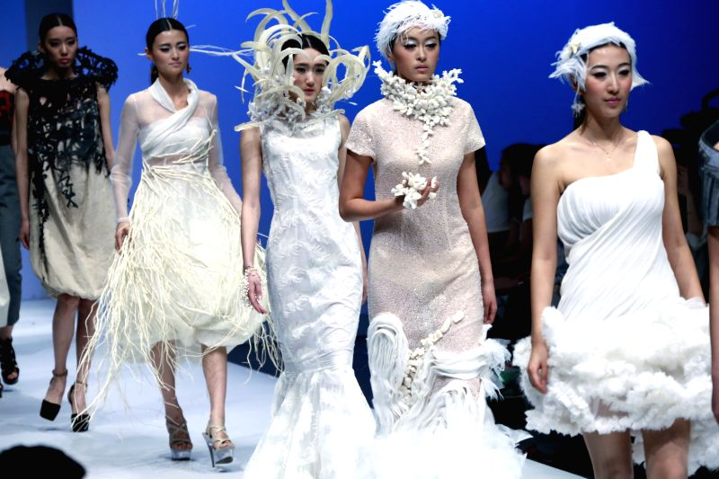 Models present creations designed by graduates from Wuhan-based Jianghan University during the 2014 China Graduate Fashion Week in Beijing, capital of China, April