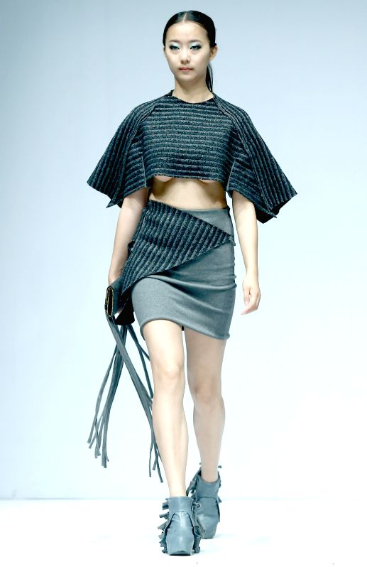 A model presents a creation designed by graduates from Soochow University during the 2014 China Graduate Fashion Week in Beijing, capital of China, April 25, 2014.