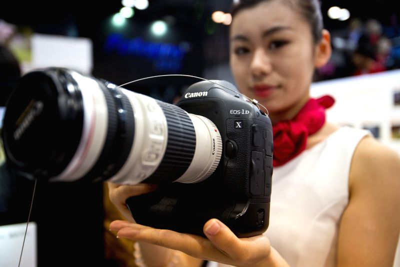 A model shows a Canon camera during the 17th China International Photograph & Electrical Imaging Machinery and Technology Fair in Beijing, capital of China, ...