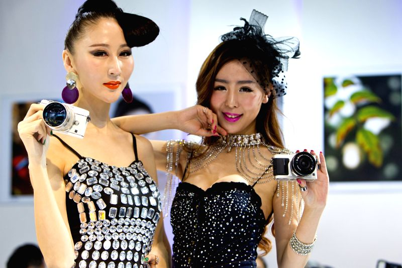 Models present Olympus cameras during the 17th China International Photograph & Electrical Imaging Machinery and Technology Fair in Beijing, capital of China, .