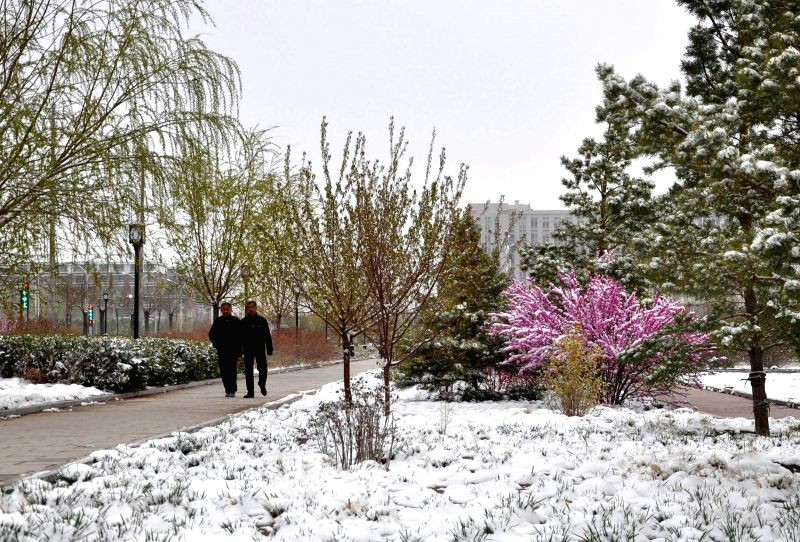 People walk by a square in Bayan Nur, north China's Inner Mongolia Autonomous Region, April 25, 2014. A snowfall hit some areas in Gansu Province and Inner ...