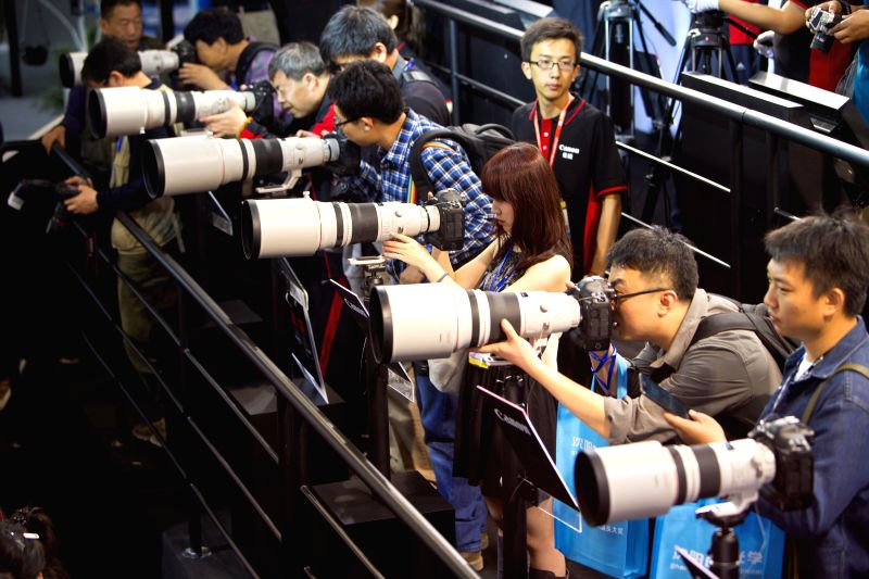 Visitors try Canon lenses during the 17th China International Photograph & Electrical Imaging Machinery and Technology Fair in Beijing, capital of China, April