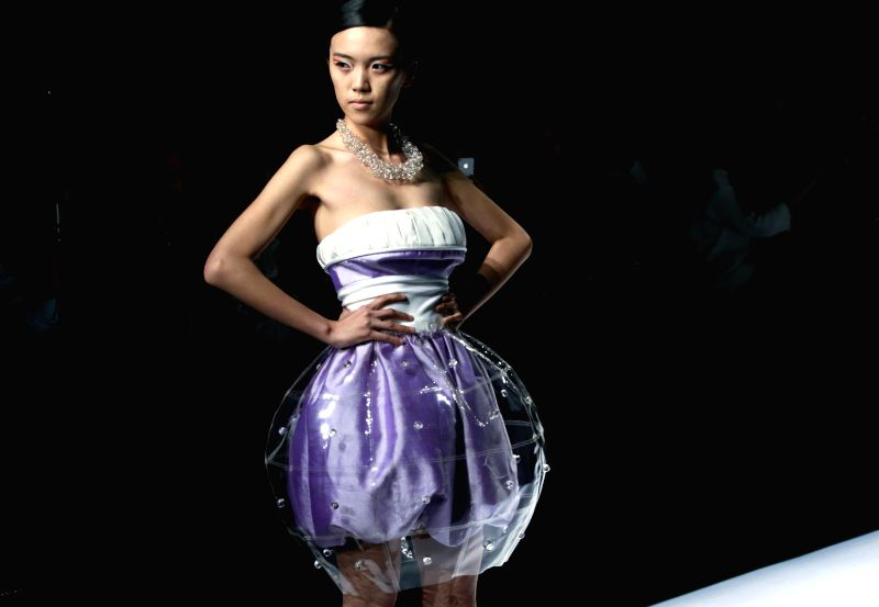 A model presents a creation designed by graduates from Raffles Design and Business School in Australia during the 2014 China Graduate Fashion Week in Beijing, ...