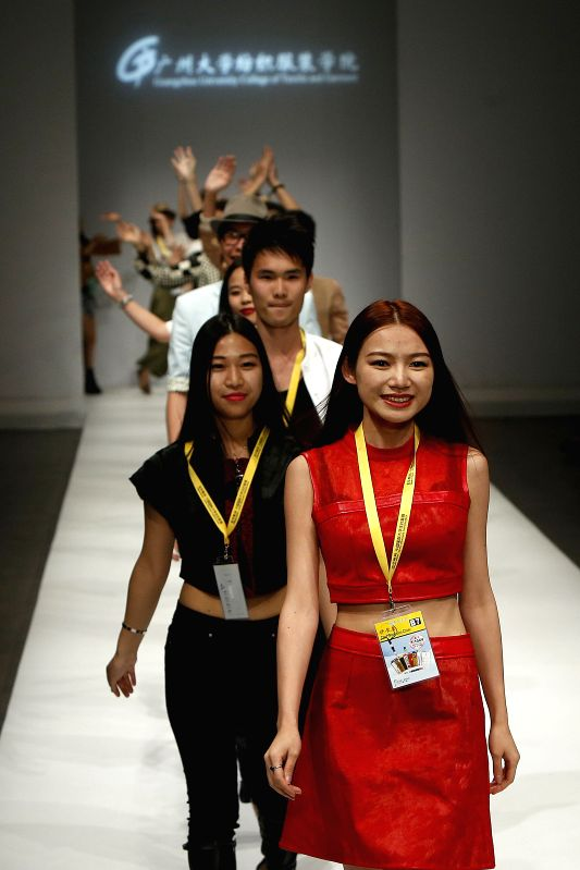 Designers from Guangzhou University College of Textile and Garment walks on the runway after their fashion show during the 2014 China Graduate Fashion Week in ...