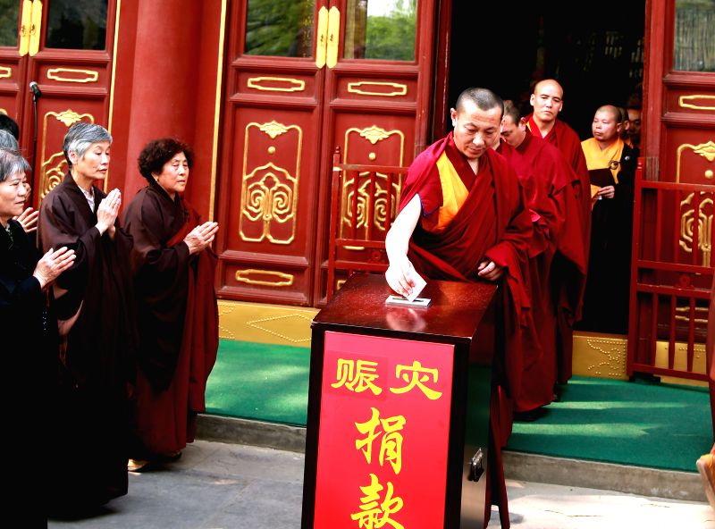 Buddhists donate money at a prayer ritual for victims of Nepal earthquake in Beijing, capital of China, April 27, 2015. More than 2.2 million yuan (354,000 U.S. ...