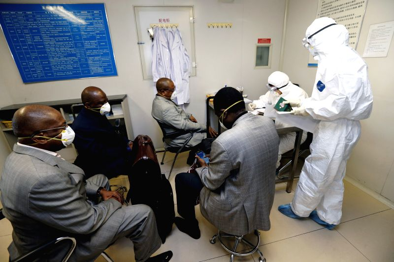 Quarantine staff members fill up questionary for four passengers who came from Ebola-infected Nigeria at the Beijing Capital International Airport in Beijing, ...