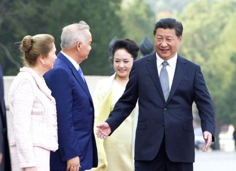 Chinese President Xi Jinping (1st R) and his wife Peng Liyuan (2nd R) greet visiting Uzbekistan's President Islam Karimov (2nd L) and his wife Tatyana Karimova ...