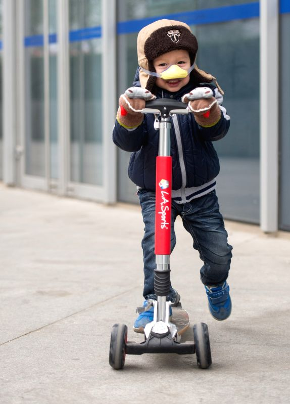 Beijing (China): A kid wears a nose mask respirator against heavy smog as he plays with a kick scooter in Beijing, capital of China, Nov. 29, 2014. China's capital city was again caught in a heavy ...