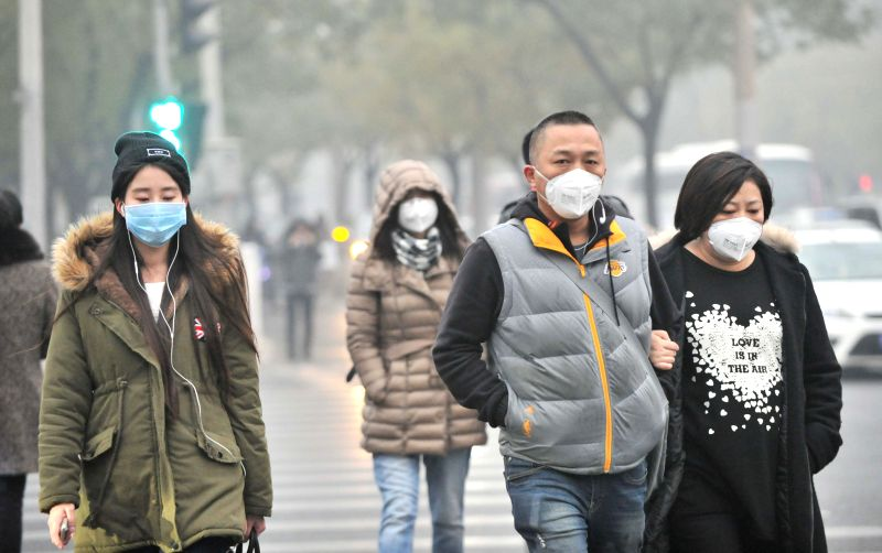 Beijing (China): Pedestrians wear facial mask respirators against heavy smog in Beijing, capital of China, Nov. 29, 2014. China's capital city was again caught in a heavy smog on Saturday. Beijing's .