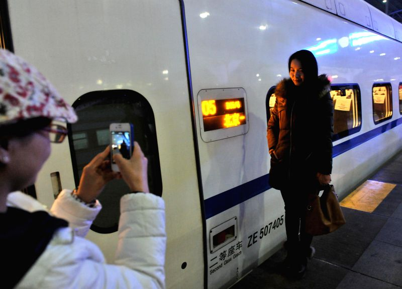 A passenger living in Yanjiao Township, Sanhe City of north China's Hebei Province, poses for photos after arriving at Beijing Railway Station by a high-speed train
