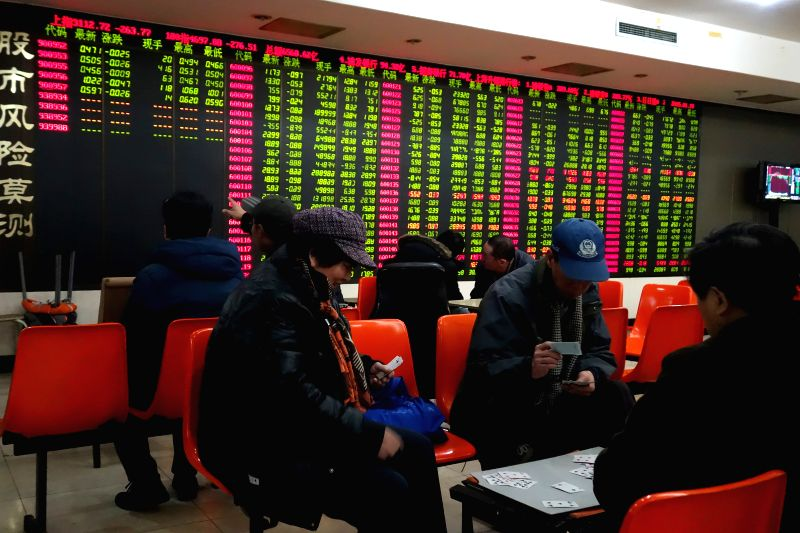 Investors play cards at a trading hall of a securities firm in Beijing, capital of China, Jan. 19, 2015. Chinese shares dived on Monday, with the key Shanghai index