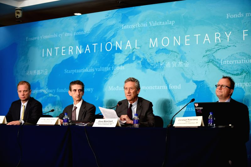 Olivier Blanchard (2rd R), IMF economic counsellor and director of the Research Department, attends a press briefing on the World Economic Outlook in Beijing, ...