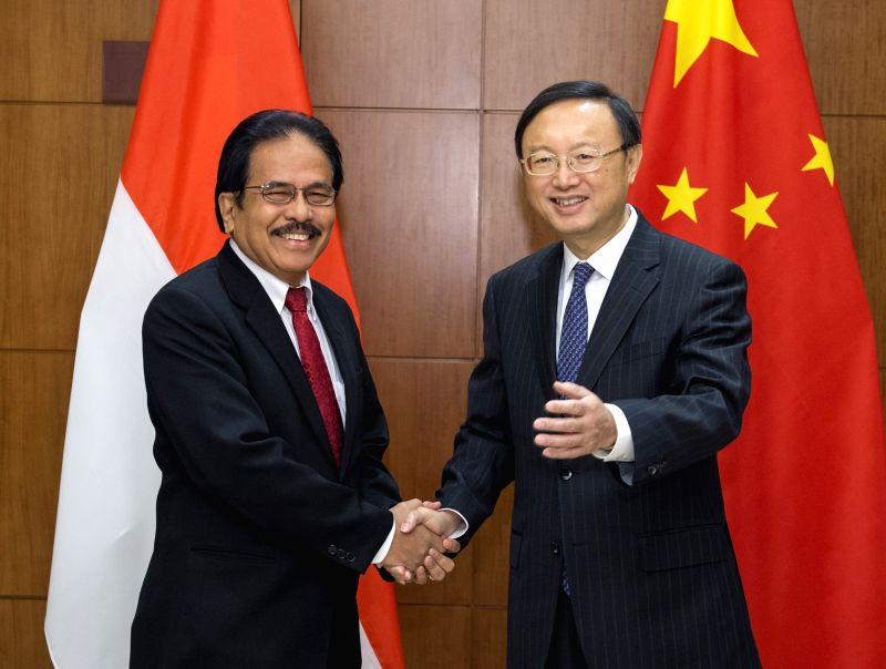 Chinese State Councilor Yang Jiechi (R) and Indonesian Coordinating Minister for Economy Sofyan Djalil shake hands during the first meeting of China-Indonesia ...
