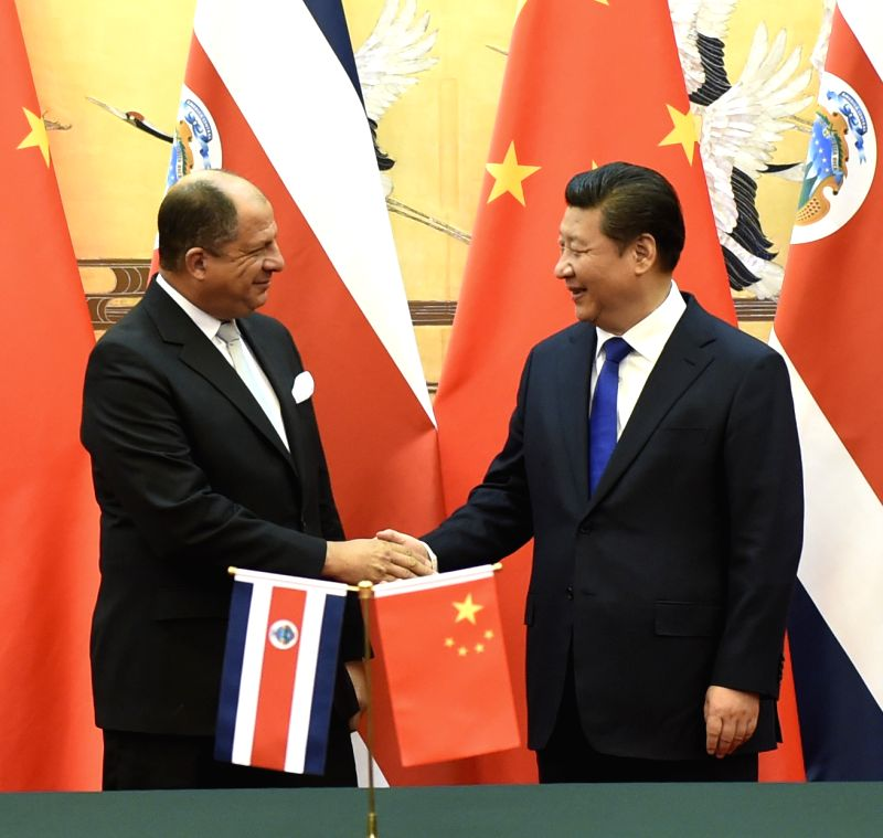 Chinese President Xi Jinping (R) shakes hands with Costa Rica President Luis Guillermo Solis after a signing ceremony in Beijing, capital of China, Jan. 6, 2015. Xi .