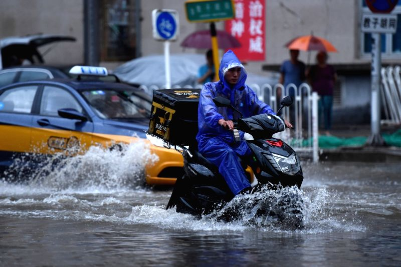 BEIJING, July 16, 2018 - A man rides on a waterlogged road in Beijing, capital of China, July 16, 2018. The city issued a rainstorm as well as flood alert Monday.