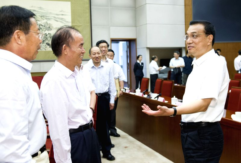 Chinese Premier Li Keqiang (R), also a member of the Standing Committee of the Political Bureau of the Communist Party of China (CPC) Central Committee, talks with .