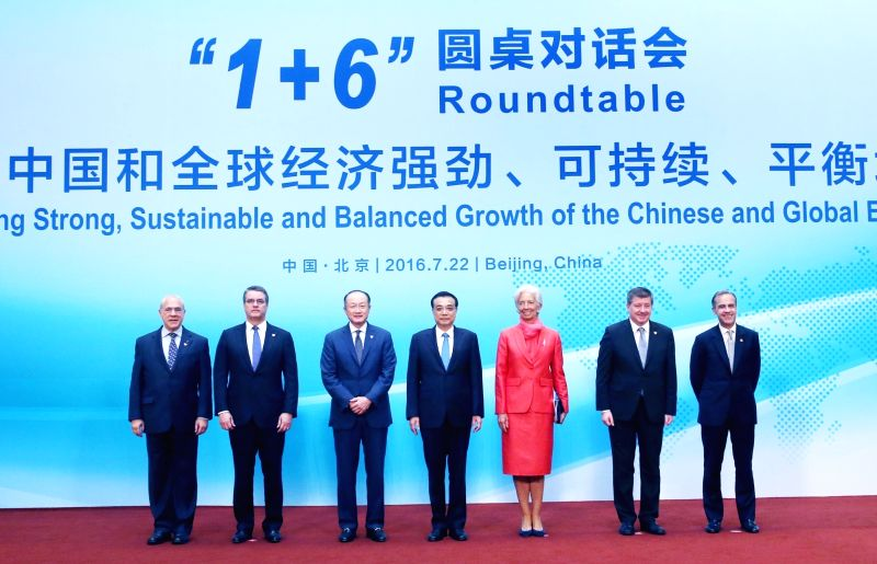 BEIJING, July 22, 2016 - Chinese Premier Li Keqiang (C) and other six chiefs of international financial institutions take a group photo before a round-table meeting at Diaoyutai State Guesthouse in ...