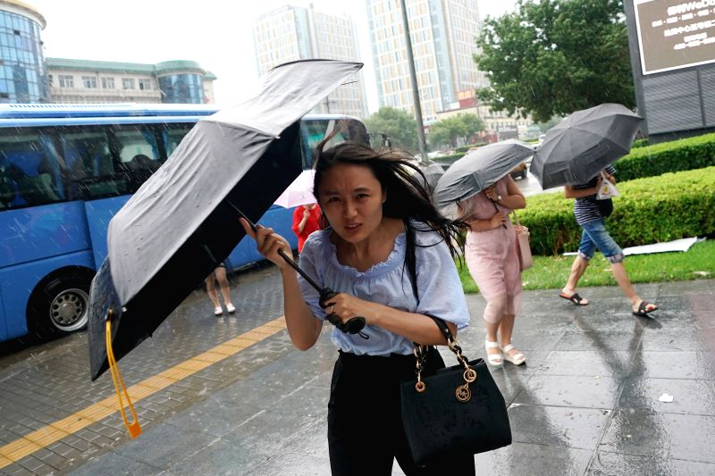 BEIJING, July 24, 2018 - Pedestrians walk in rain at Qingnian Road in Chaoyang District in Beijing, capital of China, July 24, 2018.  Beijing issued a yellow warning for heavy rain on Tuesday morning.