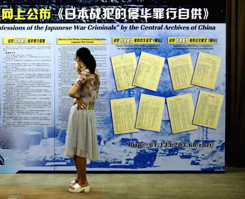 A reporter views a poster board before a press conference in Beijing, capital of China, July 3, 2014. Confessions made by 45 Japanese war criminals tried and ...