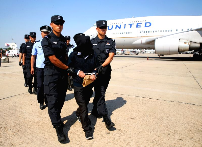 BEIJING, June 1, 2017 - A criminal suspect walks under police escort at Beijing Capital International Airport, in Beijing, China, June 1, 2017. The United States law enforcement handed over a ...