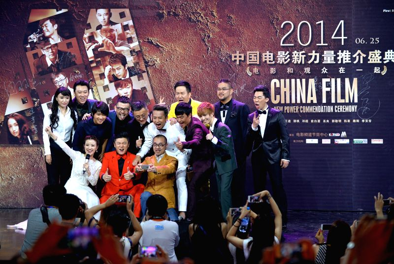 Guests and anchormen pose for photos during China Film New Power Commendation Ceremony in Beijing, capital of China, June 25, 2014. Ten young directors brought ...