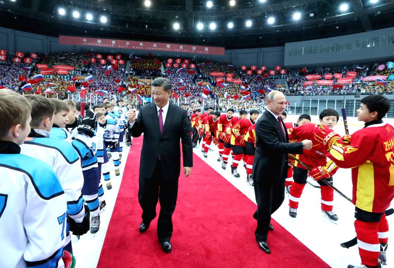BEIJING, June 9, 2018 - Chinese President Xi Jinping and his Russian counterpart Vladimir Putin bump fists with players during an ice hockey friendly match between Chinese and Russian youth teams at ...