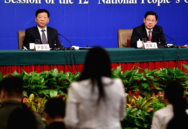 Yin Weimin(L), minister of human resources and social security, and his deputy Hu Xiaoyi give a press conference during the third session of China's 12th China's ...