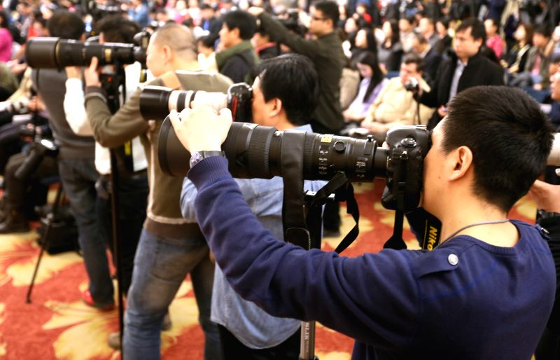 Journalists work at a press conference given by Zhu Weiqun, Huang Jiefu, Hu Xiaoyi, Li Yanhong, Yu Minhong, members of the 12th National Committee of the Chinese ...