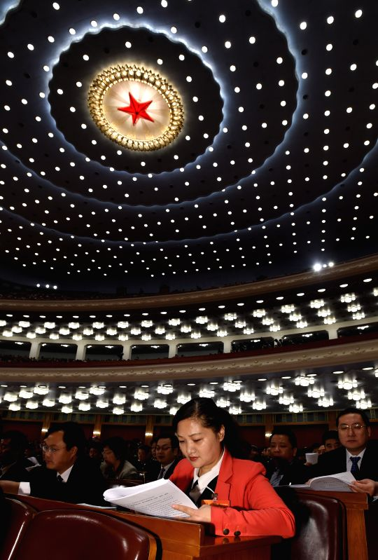 Deputies to the 12th National People's Congress (NPC) listen at the third plenary meeting of the third session of the 12th NPC at the Great Hall of the People in ...