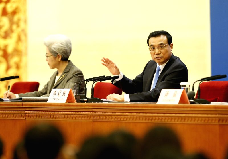 Chinese Premier Li Keqiang (R) speaks at a press conference after the closing meeting of the third session of China's 12th National People's Congress (NPC) at the ...