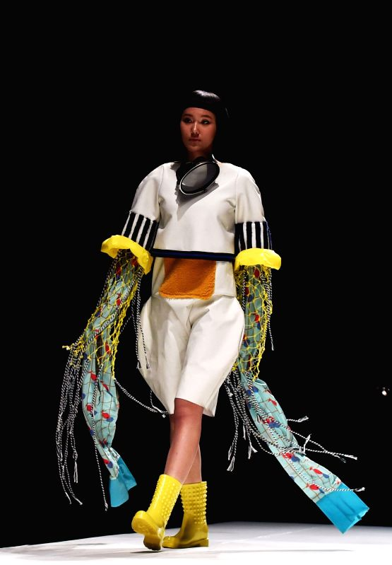 """A model presents fashion creations designed by graduates of Beijing Institute of Fashion Technology during the """"Already Here"""" fashion week in Beijing, ..."""