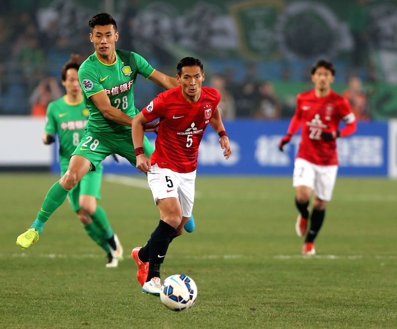 Zhang Chengdong (front L) of China's Beijing Guoan vies with Makino Tomoaki of Japan's Urawa Red Diamonds during a Group G match at the AFC Champions League 2015 ...