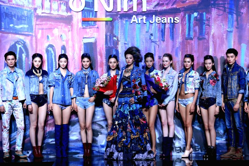 Models present creations of D'Nim art jeans by designer Chen Wen during the China Fashion Week Autumn/Winter 2015/2016 in Beijing, capital of China, March 27, ...