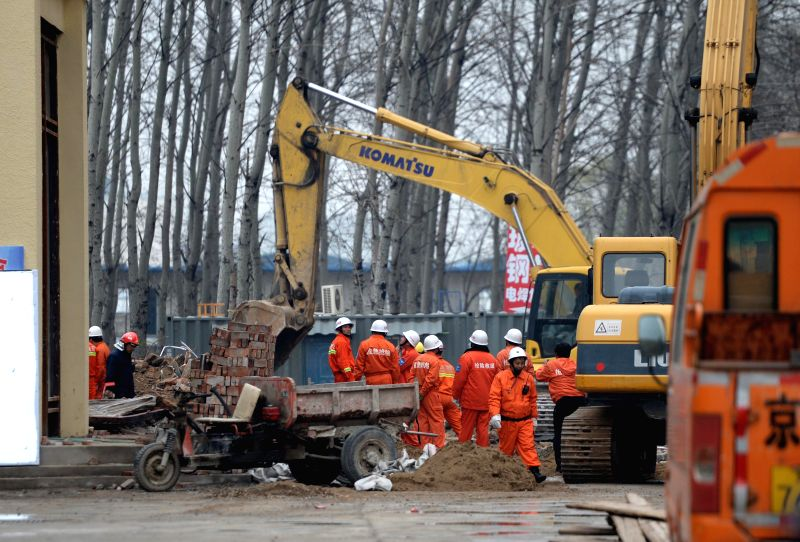Rescuers work at the accident site where a building collapsed in Beijing, Capital of China, March 31, 2015. Two workers were trapped in the collapse which occurred ...