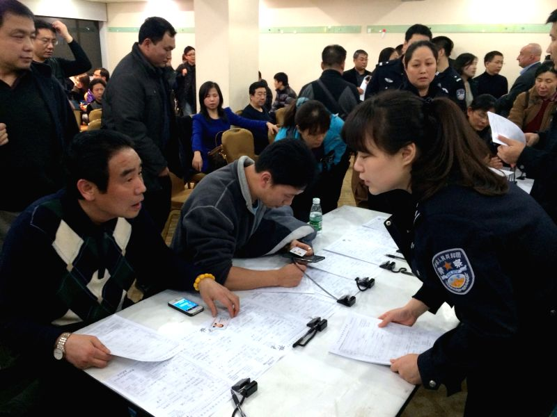 A policewoman of the exit-entry administration under Beijing Municipal Public Security Bureau guides relatives of passengers on the missing Malaysian Airline flight