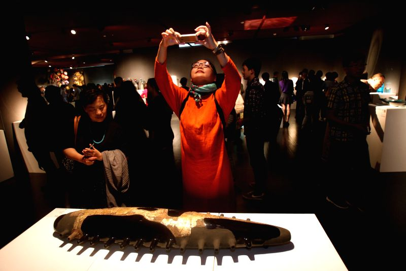 Visitors look at an artwork during an exhibition of Chinese contemporary arts and crafts in Beijing, capital of China, May 10, 2014. A total of 200 pieces of ...
