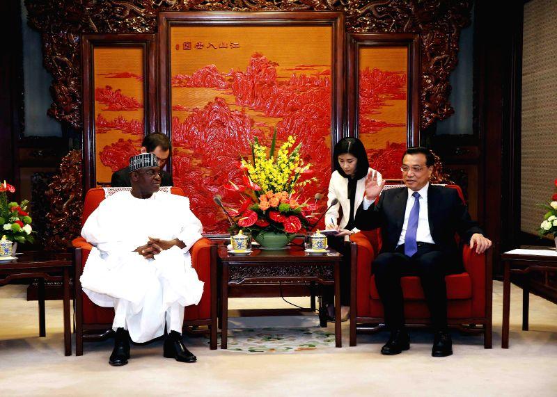 Chinese Premier Li Keqiang (1st R) meets with visiting Nigerian Senate President David Mark in Beijing, capital of China, May 13, 2014.  ...