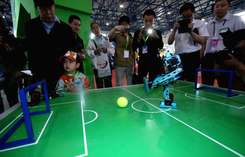 Visitors watch a robot footballer at the 17th China Beijing International High-Tech Expo (CHITEC) in Beijing, capital of China, May 14, 2014. The annual technology ..