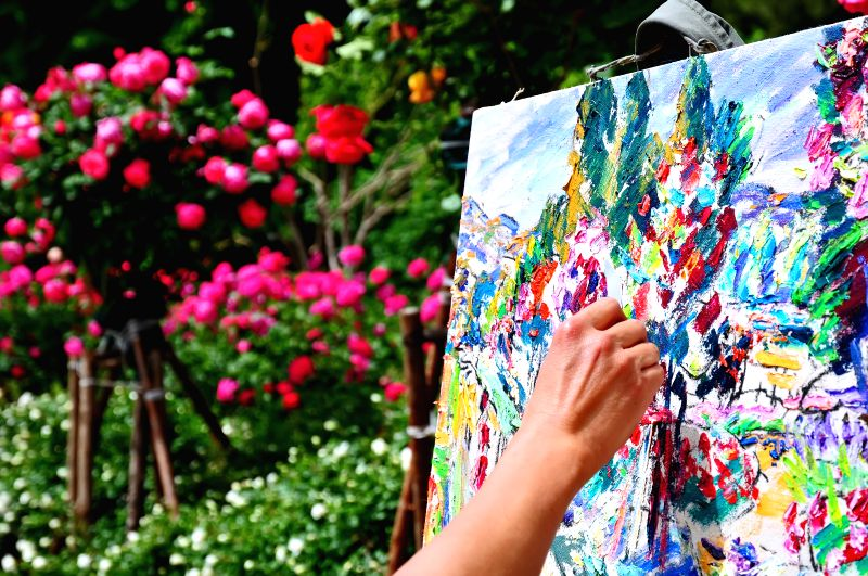 A painter makes sketches of Chinese roses during the Chinese rose cultural festival at the Beijing Botanical Garden in Beijing, capital of China, May 15, 2014. ...