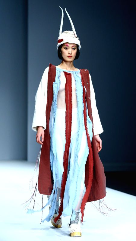 A model presents a creation by students from the School of Arts of South China Agricultural University during the China Graduate Fashion Week 2015 in Beijing, ...
