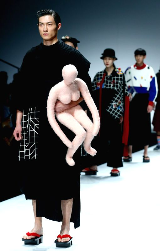 A model presents a creation by the students from the School of Industrial Design of Guangzhou Academy of Fine Arts during the China Graduate Fashion Week 2015 in ...