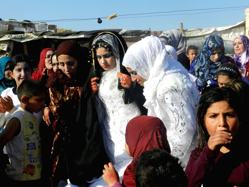A Syrian bride (C) is surrounded by relatives and friends during her wedding at a refugee camp in eastern Lebanon, on April 17, 2014. According to the recent report