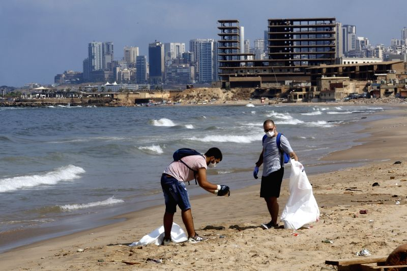 """BEIRUT, Aug. 25, 2018 (Xinhua) -- Lebanese environmental activists clean the beach of """"San Michel"""", which faces serious pollution, at south of Beirut, Lebanon, Aug. 25, 2018. (Xinhua/Bilal Jawich/IANS)"""
