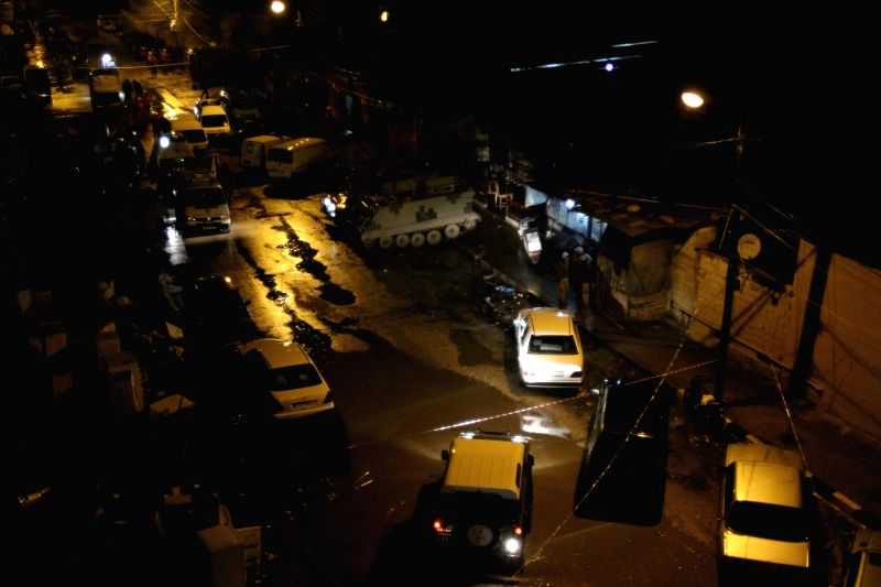 Rescue vehicles gather besides the bombing site of a popular cafe in Lebanon's northern port city of Tripoli, Jan. 10, 2015. Seven people were killed and several ...