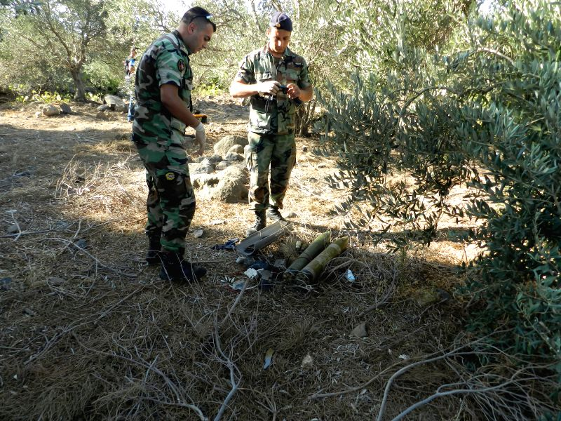 Lebanese army soldiers check two unused rockets on the outskirts of Lebanon's southern town of Mari in Hasbaya, July 11, 2014. Two rockets were fired on northern ...