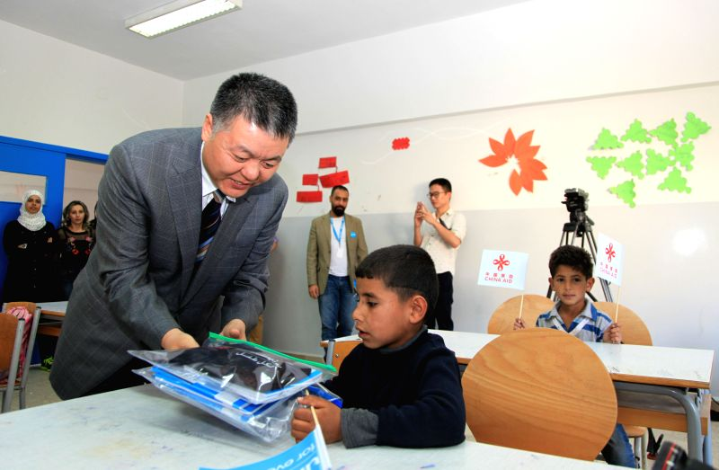 BEIRUT, May 12, 2017 - China's ambassador to Lebanon Wang Kejian delivers school supplies to a Syrian refugee child at a school in Bekaa town, Lebanon, on May 12, 2017. China's ambassador to Lebanon ...