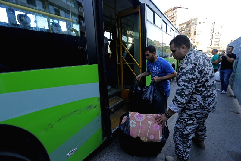 BEIRUT, Oct. 10, 2019 (Xinhua) -- Syrian refugees go on a homebound trip by bus from Beirut, Lebanon on Oct. 10, 2019. Around 1,000 Syrian refugees returned home from Lebanon on Thursday, the National News Agency reported. Syrians from different citi