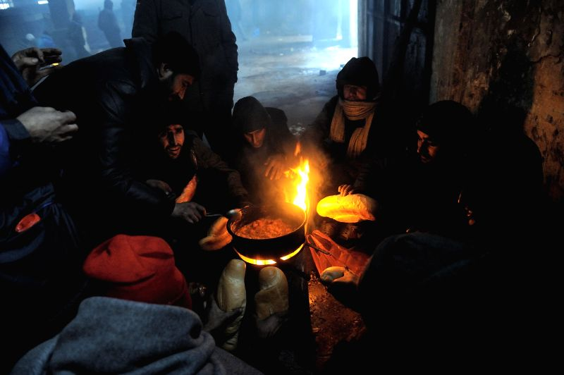 BELGRADE, Jan. 11, 2017 - A group of migrants prepare food on fire in a shelter at an abandoned warehouse in freezing weather in Belgrade, Serbia, on Jan. 11, 2017. Low temperatures and long-lasting ...